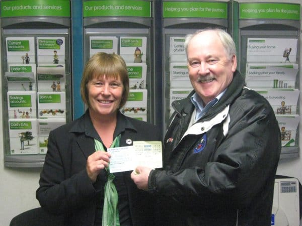 Dennis Fenton presents a cheque for £1750 to Loons Lottery Jackpot winner, Pamela Elms